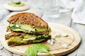 stock photo of sandwich  - grilled rye sandwiches with cheese spinach pesto avocado and goat cheese - JPG