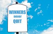 stock photo of quit  - Winners Never Quit motivational quote written on white road sign isolated over clear blue sky background - JPG