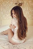 picture of bare butt  - Girl model with long brown hair style wearing in white lace sexy lingerie sitting on bed in luxury modern interior - JPG