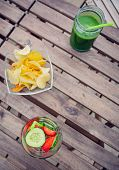foto of infusion  - Top view of infused fruit water cocktails and green vegetable smoothies over a wooden table outdoors - JPG