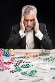 image of poker hand  - Man in years sitting at poker table and considering poker strategy with his hands on temples - JPG