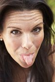 foto of sticking out tongue  - Head And Shoulders Portrait Of Woman Sticking Out Tongue - JPG