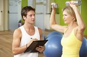 stock photo of encouraging  - Woman Exercising Being Encouraged By Personal Trainer In Gym - JPG