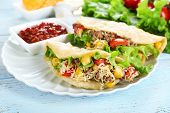 stock photo of tacos  - Tasty taco with tomato dip on plate and vegetables on table close up - JPG