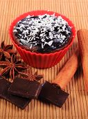 foto of chocolate muffin  - Homemade delicious fresh baked chocolate muffins with desiccated coconut in red silicone cups pieces of chocolate star anise and stick of cinnamon - JPG