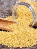 stock photo of millet  - Heap of yellow millet groats spilling out of glass jar on wooden background concept for healthy eating and nutrition - JPG