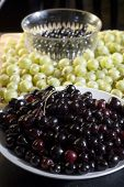 picture of black-cherry  - Bowls of dark red cherries and black currants, surrounded by green gooseberries on a wooden chopping board ** Note: Shallow depth of field - JPG