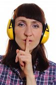 stock photo of silence  - Female construction worker wearing protective headphones holding index finger to lips and showing silence sign safety at work and ear protection - JPG