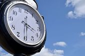 foto of puffy  - Face of outdoor clock telling the time of three thirty against a blue sky with white puffy clouds - JPG