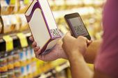 picture of supermarket  - Man Scanning Voucher Code In Supermarket With Mobile Phone - JPG
