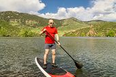 stock photo of horsetooth reservoir  - male paddler enjoying stand up paddling on a sunny summer day  - JPG
