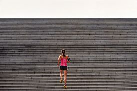 stock photo of step-up  - sporty woman working out running up stairs outdoors for morning workout - JPG
