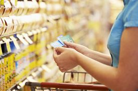 pic of grocery cart  - Woman In Grocery Aisle Of Supermarket With Coupons - JPG
