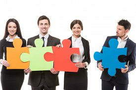 picture of four  - Image of four confident business people wanting to put pieces of puzzle together - JPG