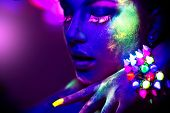 Fashion model woman in neon light, portrait of beautiful model girl with fluorescent powder make-up, poster