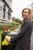 Woman putting plastic waste in garbage bin