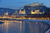 stock photo of mozart  - illuminated city salzburg in austria at winter evening - JPG