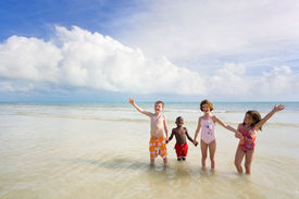stock photo of children beach  - four young children of diverse backgrounds playing at the beach - JPG