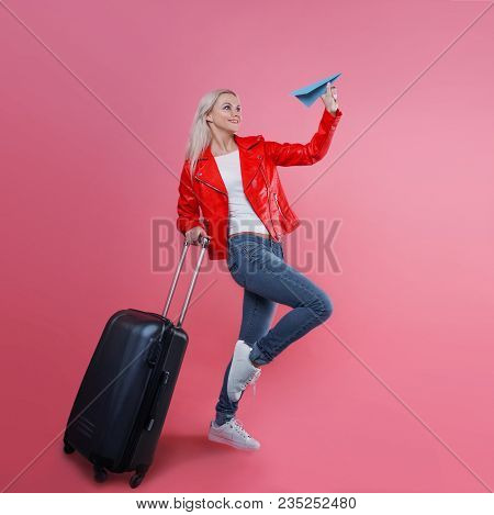 poster of Concept, Ready To Travel. Happy Young Woman With Travel Suitcase Launches Paper Airplane. Blonde Tou