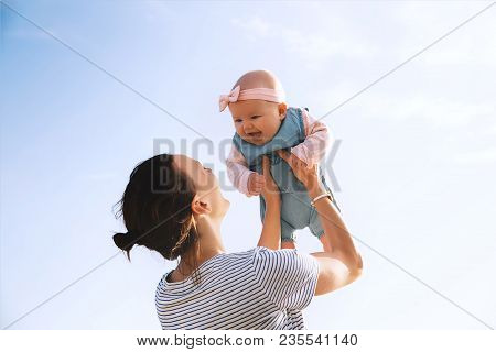 poster of Young Mother Throws Up Baby In The Sky, Summer Outdoors. Happy Mom And Cute Smiling Baby Girl. Posit