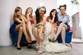 Bride sitting with envious girlfriend in professional fashion designer studio