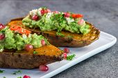 Baked Sweet Potatoes With Guacamole, Feta Cheese And Pomegranate - Bataty - Closeup poster