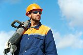 Portarait of positive Builder worker with pneumatic hammer drill equipment over blue sky