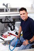Jovem bonito encanador fazendo reparação na cozinha.