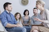Upset Man Sitting In Group Therapy And Listening To The Psychologist With Concerned Family In The Ba poster