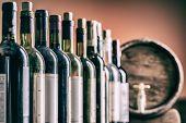 Wine bottles in row and oak wine keg. poster