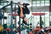 Young Athlete Turn Upside Down Working Out Indoor Gym Doing Endurance Exercises poster