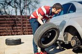 Changing A Flat Car Tire In The Backyard. Tire Maintenance, Damaged Car Tyre Or Changing Seasonal Ti poster