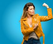 Beautiful young woman pointing biceps expressing strength and gym concept, healthy life its good, bl poster