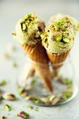 Green Ice Cream In Waffle Cone With Chocolate And Pistachio Nuts On Grey Stone Background. Summer Fo poster