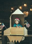 Kid In Helmet Sit In Cardboard Hand Made Rocket With Usa Flags. Child Boy Play American Astronaut. C poster