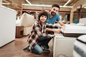 Bearded Man With Young Son Is Testing Mattress For Softness. Testing Softness Of Mattress. Choosing  poster