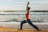 Woman doing Hatha yoga asana Virabhadrasana 1 Warrior Pose outdoors on ocean beach on sunset. Kerala poster
