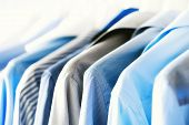 Blue Color Clothes. Male Clothes, Jackets And Shirts Hanging On Clothes Rail. Copy Space. Banner. poster