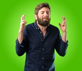 Young hipster man with big beard with crossed fingers asking for good luck over green background poster