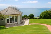 curve way leads to elegant gazebo with sea and blue sky background