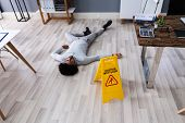 Mature Man Falling On Wet Floor In Front Of Caution Sign At Office poster