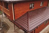 Modern Roof Made Of Metal. Corrugated Metal Roof And Metal Roofing. House With A Brown Metal Roof. poster