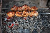 cook shish kebab on skewer under hot coal