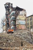 Destrucción de edificios de apartamentos viejos y excavadora