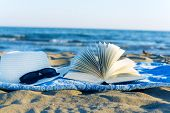 Straw hat ,sunglasses, book and seashell in the sand