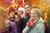 Happy friends drinking mulled wine and eating crystalized appels on German Christmas Market poster