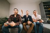 Cheerful Company Of Friends Emotional Playing Video Games Have Fun And Drink Beer At The Weekend In  poster