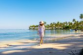 Traveler Girl Walking In White Dress On A Tropical Beach. Young Girl Traveler Walking In Nature. Tra poster