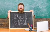 Teacher Or School Principal Welcomes With Blackboard Inscription Back To School. Welcome Back. Begin poster