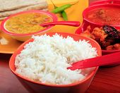 stock photo of tadka  - Traditional indian rice and chapatti meals with spicy daal curry and other vegetarian dishes choseup photo